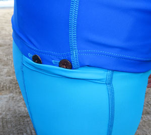 Buttons on the leggings or shorts and button holes on the Tuga snorkel line shirts connect the two garments so the shirt does not ride up and let the sun burn your back.