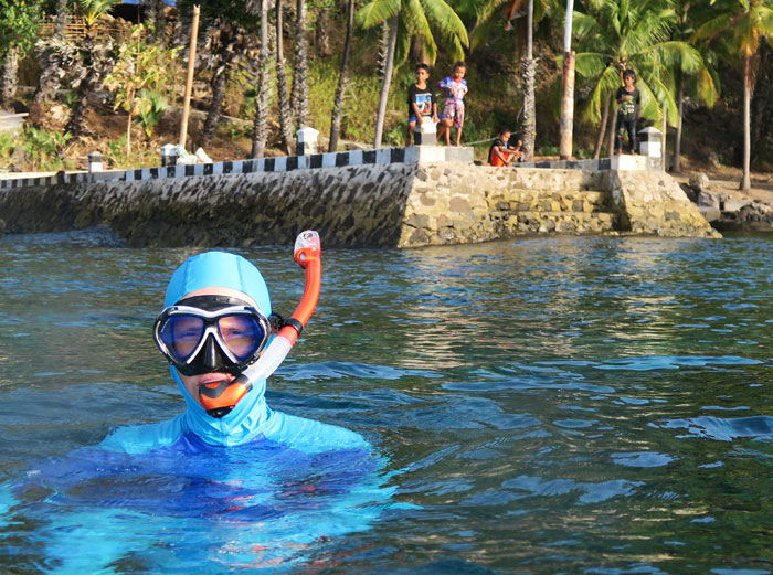 Nicole snorkeling in Alor with curious kids from the local village watching.