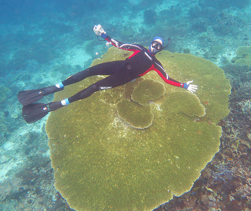 Galen diving down to show how big this table coral is with his favorite snorkel, the Riffe Stable.