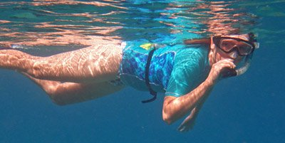 Snorkeler wearing a waterproof snorkeling box belted around her waist.