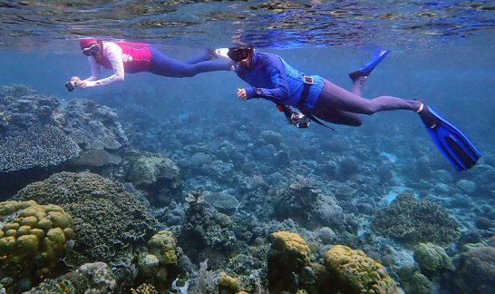 Nicole and Galen in Indonesia in their Tuga Sunwear hooded snorkeling rash guards and leggings.
