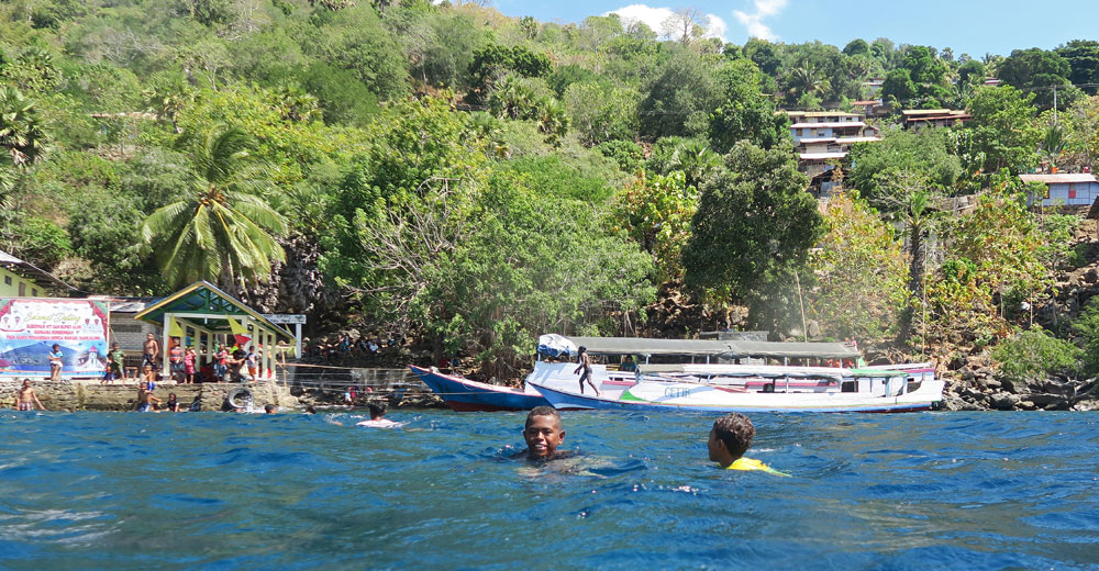 More kids swimming with us snorkelers in front of a village.