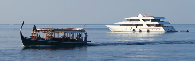 Our Maldives snorkeling liveaboard, and a dhoni, very much like the small boat that we snorkeled from.