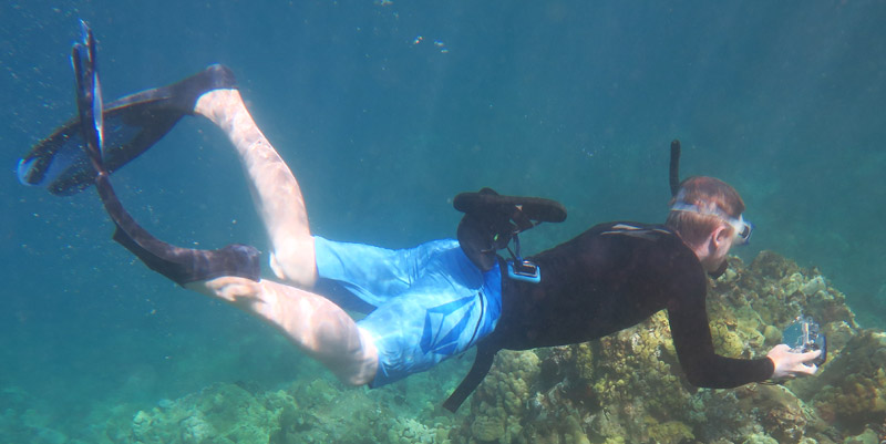 Galen's snorkeling shoes floating above his belt he attaches them to on a snorkel.