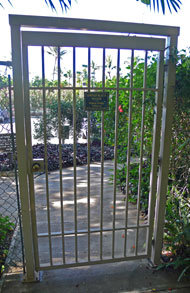 Gate from the south parking lot to the cement path leading down to Poolenalena Beach.